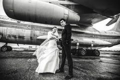 Le couple magnifique de mariage pose sous une aile énorme d'un avion Images stock