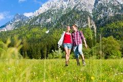 Le couple marche dans le pré avec la montagne Photographie stock libre de droits
