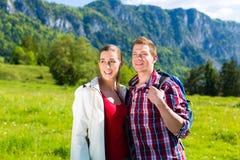Le couple marche dans le pré avec la montagne Images libres de droits