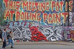 Le couple marche devant un graffiti énorme Photos libres de droits