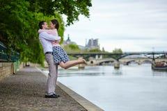 Le couple marche par l'eau à Paris Photos stock
