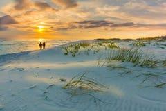 Le couple marche sur la plage au coucher du soleil Photos libres de droits