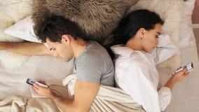 Le couple marié se trouve de nouveau au dos dans le lit avec des téléphones portables Mouvement lent clips vidéos