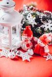 Le couple mignon de petits bonhommes de neige se tient près de la lanterne féerique blanche Photo stock