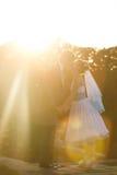 Le couple mignon tient des mains et les embrasse sur le sunse de fond Photo libre de droits