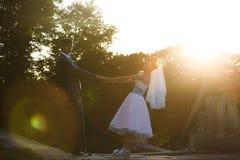 Le couple mignon tient des mains et sourit sur le sunse de fond Image stock