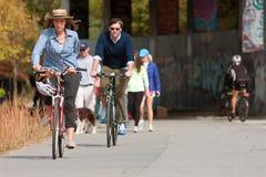 Le couple monte des vélos le long de traînée de développement urbain à Atlanta photo libre de droits