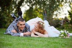 le couple Neuf-marié se trouve sur une herbe Image libre de droits
