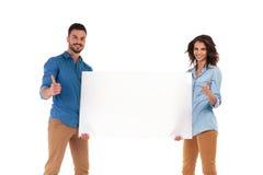 Le couple occasionnel tenant la publicité vide fait le signe correct Image stock