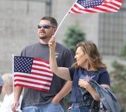 Le couple ondule les drapeaux américains au rassemblement pour fixer nos frontières Image libre de droits