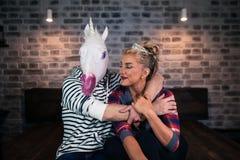 Le couple peu commun célèbre la pendaison de crémaillère Jeune femme heureuse avec l'homme drôle photo libre de droits