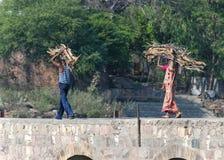 Le couple porte le bois de chauffage sur la tête au-dessus du pont dans Orchha, Inde Photographie stock libre de droits