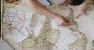 Le couple prévoit des vacances utilisant une carte du monde Pointage aux endroits de carte à visiter dans Anerica du sud banque de vidéos