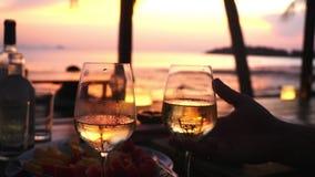 Le couple prend deux verres dans leurs mains avec du vin blanc contre le coucher du soleil à la mer Mouvement lent, 1920x1080 banque de vidéos