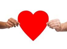 Le couple remet le coeur de rouge de fixation Photographie stock libre de droits
