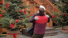 Le couple romantique de datation sur Noël juste, homme tourne son amie étreinte autour, arbre de Noël est dans clips vidéos