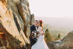 Le couple romantique de nouveaux mariés se tenant dans le coucher du soleil s'allume avec le paysage majestueux de montagne comme Image libre de droits