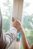 Le couple romantique tenant des mains devant la fenêtre avec la pluie chute Image stock