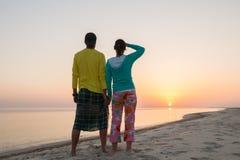 Le couple romantique, tenant des mains, se tient sur la plage Photo stock