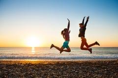 Le couple saute sur la plage au-dessus du lever de soleil Image stock