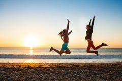 Le couple saute sur la plage au-dessus du lever de soleil Image libre de droits