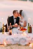 Le couple se reposant de nouveaux mariés embrasse derrière l'ensemble de pique-nique décoré des bougies brillantes dans des boute Photo libre de droits