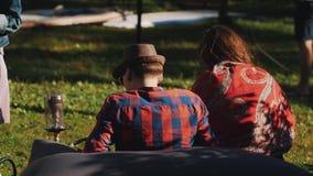 Le couple se reposant sur l'herbe dehors en nature fume le narguilé Les gens marchent par clips vidéos