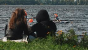 Le couple se reposant sur la montre d'herbe en tant que deux surfers monte à travers l'eau devant eux clips vidéos