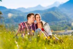Le couple se repose dans le pré avec la montagne Images stock