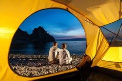 Le couple se repose près de la tente Photographie stock libre de droits