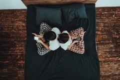 Le couple se repose sur le lit et utilise des téléphones portables photographie stock