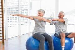 Le couple supérieur faisant l'étirage s'exerce sur des boules de forme physique Image stock