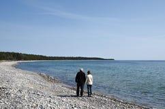 Le couple supérieur marche le long de la côte Photo libre de droits