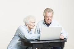 Le couple supérieur regarde des factures concernées Image stock