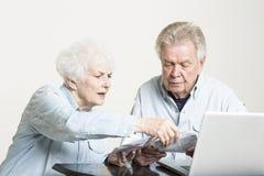 Le couple supérieur regarde des factures concernées Images stock