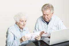Le couple supérieur regarde des factures concernées Photos libres de droits