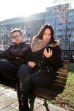 Le couple sur un parc, ami est ennuyé et femme à l'aide du smartphone Photographie stock libre de droits