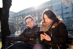 Le couple sur un parc, ami est ennuyé et femme employant un smartphon Images stock