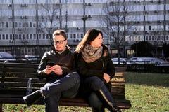 Le couple sur un parc, femme est ennuyé et ami employant un smartphon Photos stock