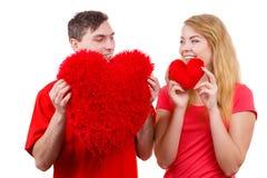 Le couple tient le symbole en forme de coeur rouge d'amour d'oreillers Images libres de droits