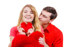 Le couple tient le symbole en forme de coeur rouge d'amour d'oreillers Photos libres de droits