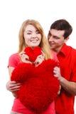 Le couple tient le symbole en forme de coeur rouge d'amour d'oreillers Images stock