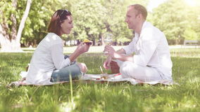 Le couple a un pique-nique dans le parc : la femme mange la mangue et les boissons d'un homme wine banque de vidéos