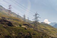 Le courant électrique domine le long du terrain de montagne pendant le jour Photos libres de droits