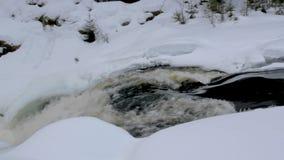 Le courant de fonte de rivière croise la vue étroite de couche épaisse de neige banque de vidéos