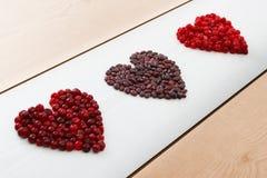 Le courant, les canneberges et les haricots rouges au coeur forment sur le conseil en bois Image libre de droits
