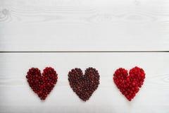 Le courant, les canneberges et les haricots rouges au coeur forment sur le conseil en bois Photos libres de droits