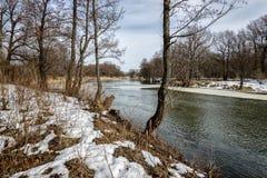 Le courant sur la rivière a libéré le canal de la glace, mais sur le rivage il reste neige photos libres de droits
