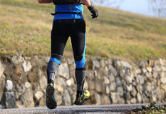 Le coureur avec des espadrilles jeûnent des courses sur la route goudronnée Photo libre de droits