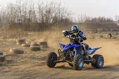 Le coureur d'ATV prend un tour pendant une course sur un terrain poussiéreux photographie stock libre de droits